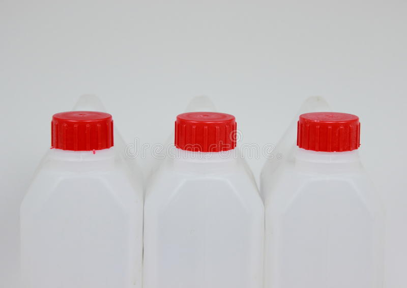 Three empty jerrycans of white plastic with red lids