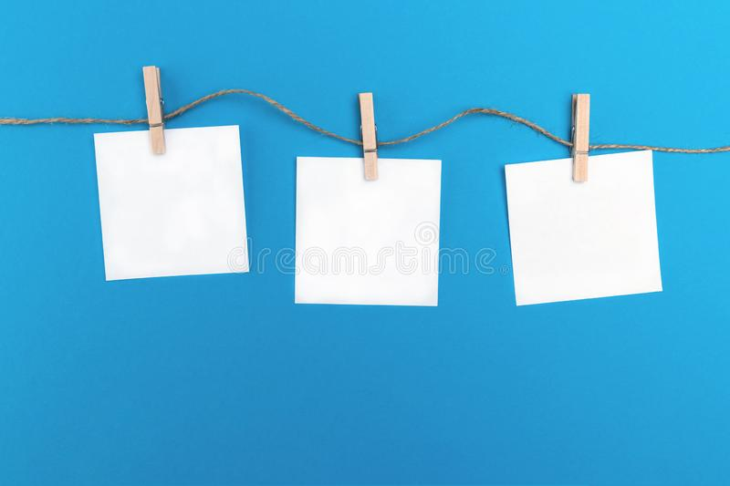Three empty little sheets of paper hold by wooden clothespins on a string. Creative concept on a blue background and free copy stock image