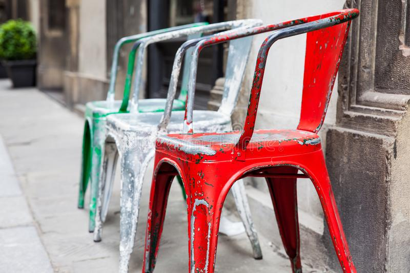 Empty rickety colorful chairs at the historical streets of Florence. Three empty rickety colorful chairs at the historical streets of Florence royalty free stock photos