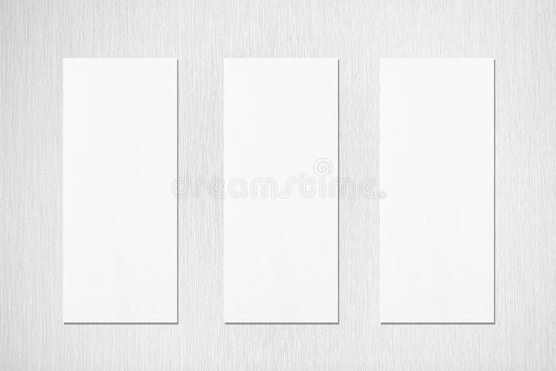 Three empty white vertical rectangle poster menu mockups. Three empty white vertical rectangle menu mockups with soft shadows on neutral light grey textured wall stock images