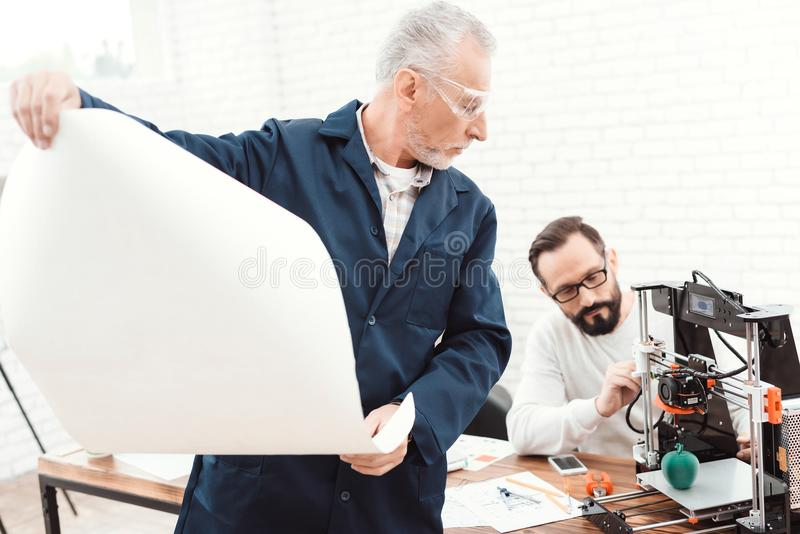 Three engineers work with a 3d printer. An elderly man in the foreground is studying a blueprint. stock images