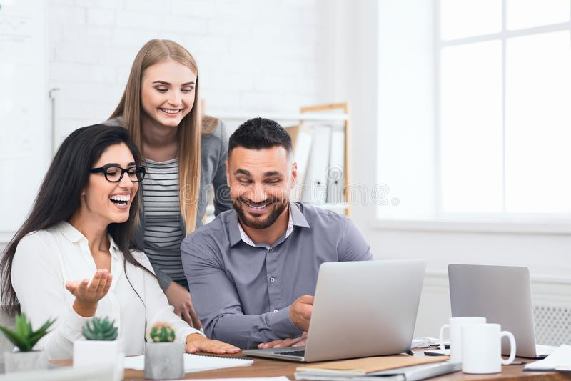 Three excited employees receiving good news on laptop stock image