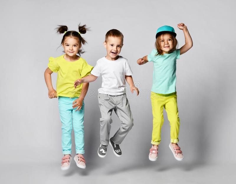 Three excited kids in fashion outfits, jumping over the light background. Two sisters and brother, friends in fashionable clothes royalty free stock photography