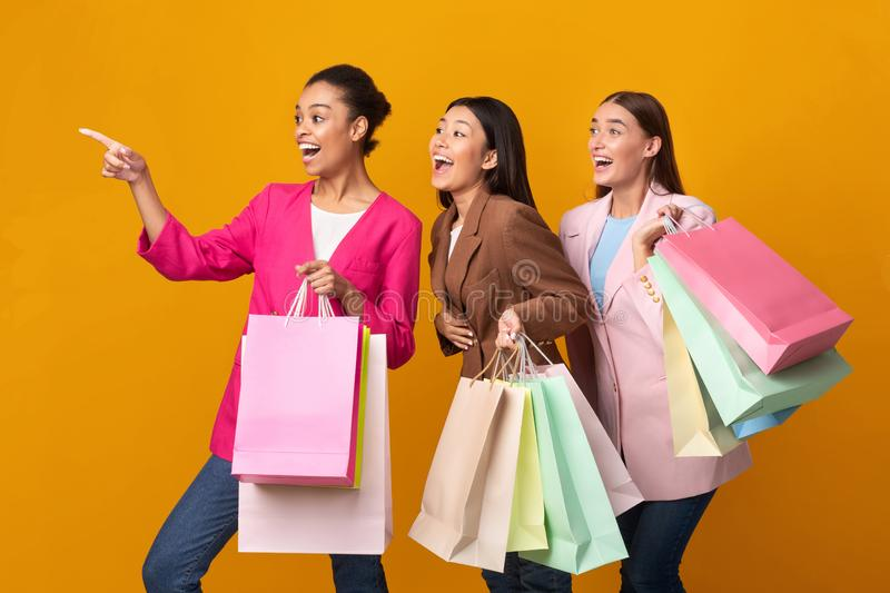 Three Excited Ladies Holding Shopper Bags Pointing Finger, Yellow Background stock photography