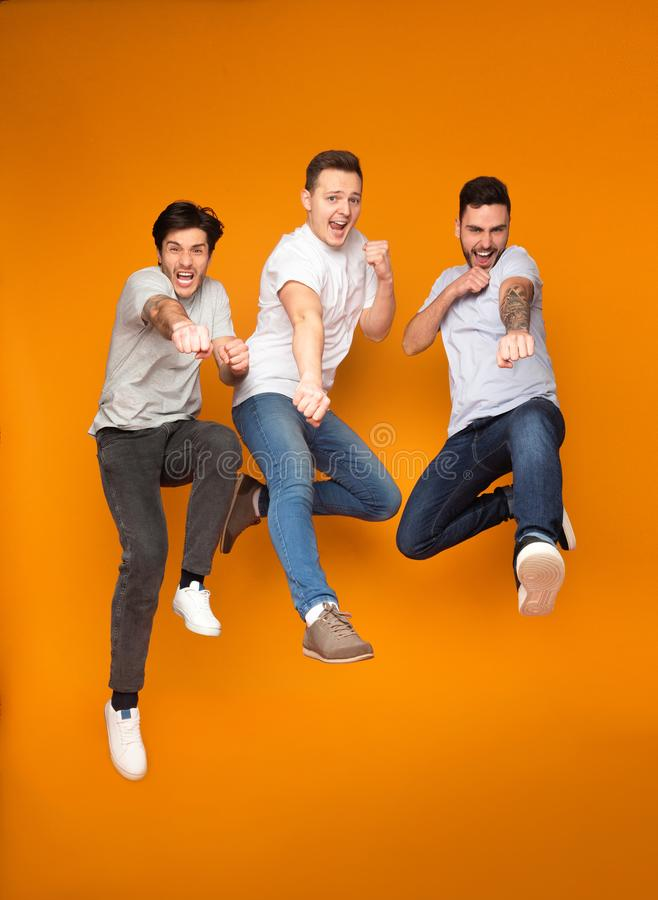 Three excited men jumping together, having fun. Over orange background royalty free stock image