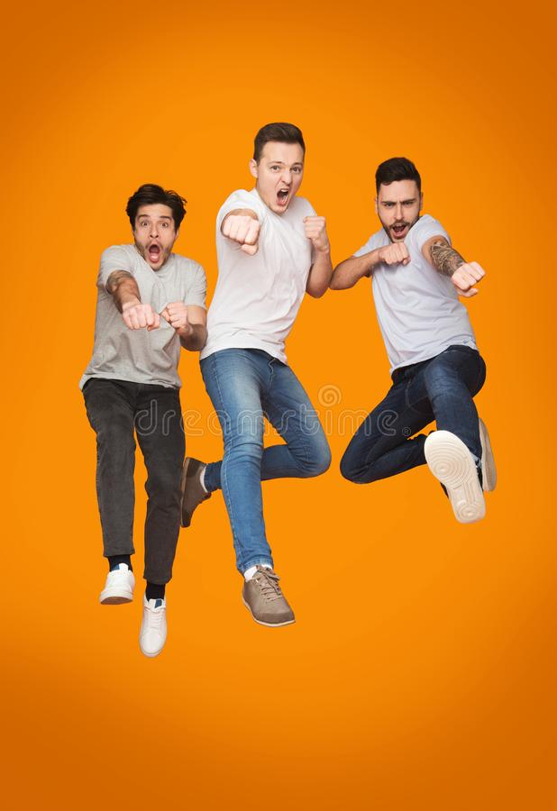 Three Excited Men Jumping Together Over Yellow Background. Three Excited Men Jumping Together Over Yellow Studio Background stock photo