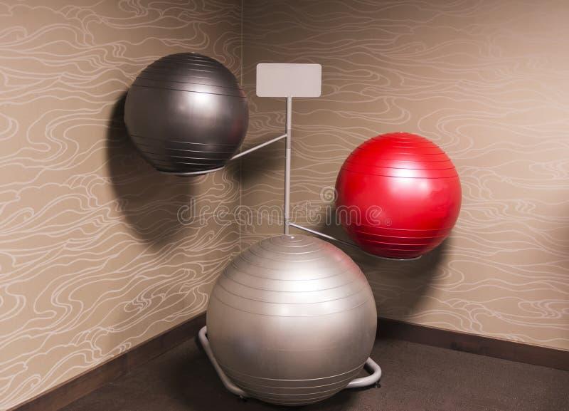 Three exercise balance balls on a rack stock photography