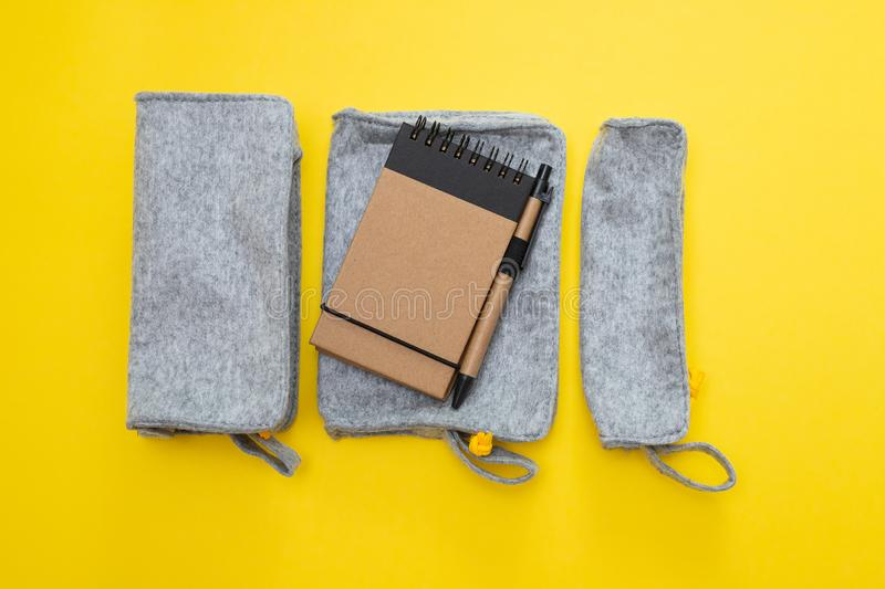 Fabric pencil cases with notepad on yellow background stock photography