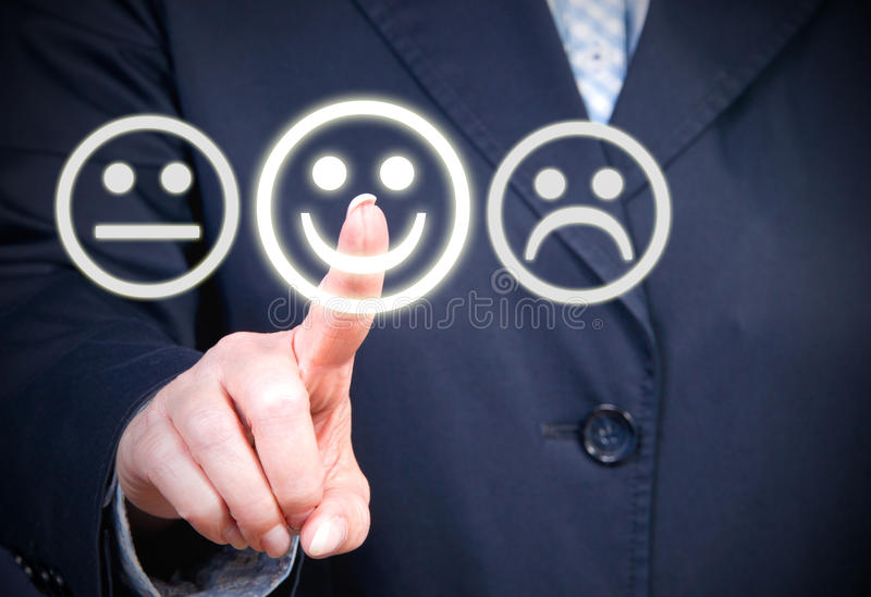 Three face symbols. Touch screen with three face symbols indicating happy, unhappy and expressing no preference with a finger pointing to the happy choice royalty free stock photos