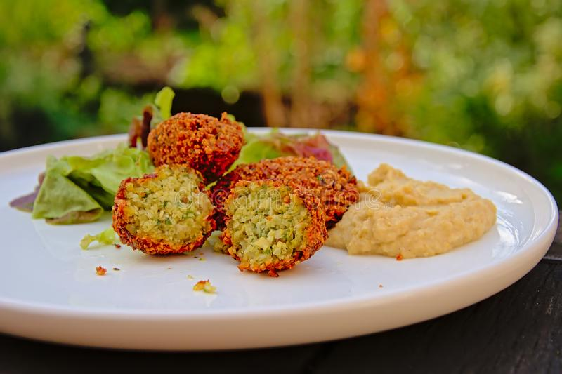 Three falafel balls, one cut in halves, humus and salad on a plate, selective focus. Three falafel balls of which one is cut in half , houmous and salad on a royalty free stock photos