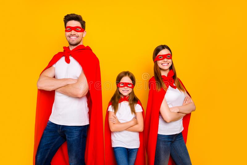 Three family members playing cartoon incredible characters wear carnival costumes isolated yellow background. Three family members playing, cartoon incredible royalty free stock photos