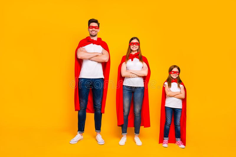 Three family members playing cartoon incredible characters wear superhero cloaks isolated yellow background. Three family members playing, cartoon incredible royalty free stock photography