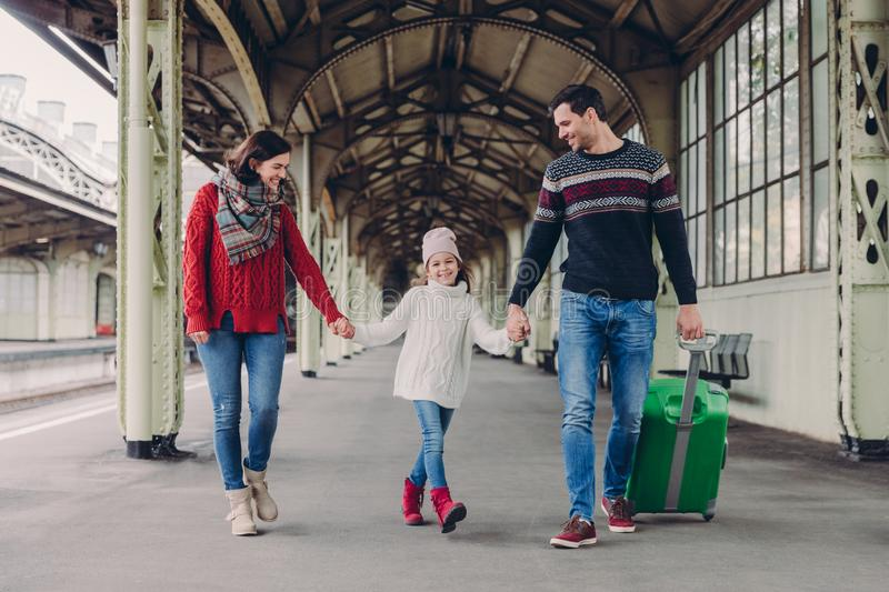 Three family members on railway station. Happy mother, daughter and father have positive facial expressions, waits for train on royalty free stock photography