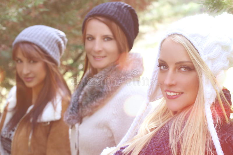 Three fashion girls posing outdoor. Three fashion girls wearing winter clothes outdoor stock image