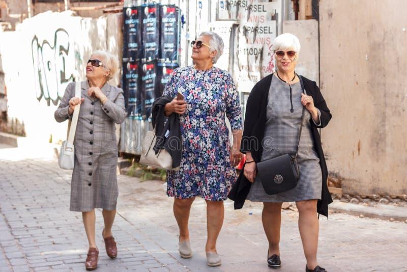 Three fashionable cheerful old ladies walk through the old town - Antalya, Turkey, 04.23.2019 stock images