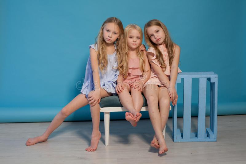 Three fashionable little girls blonde girlfriends sister portrait stock images
