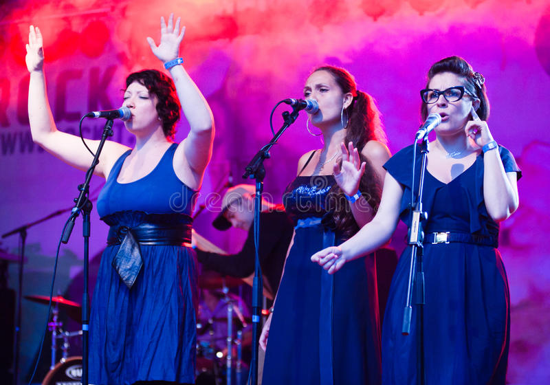 Three female choristers singing. Three female vocalist from Ghemon + Soul Combo Band perform live on stage during a music festival in Milan on June 11, 2011 royalty free stock photos