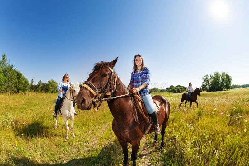 Three female equestrians riding horses in field. Three young female equestrians riding beautiful horses in flowery meadow stock photography
