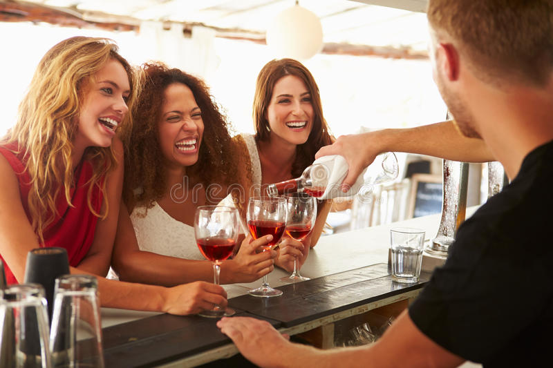Three Female Friends Enjoying Drink At Outdoor Bar stock images