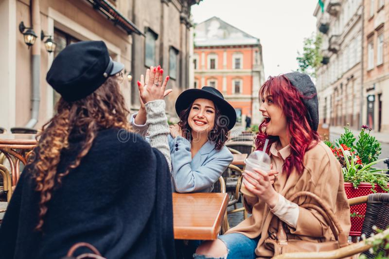 Three female friends having drinks in outdoor cafe. Woman giving high five to her best girlfriend royalty free stock images