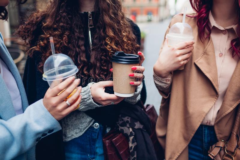 Three female friends having drinks outdoors. Women clinking coffee, orange juice and tea cups stock photography