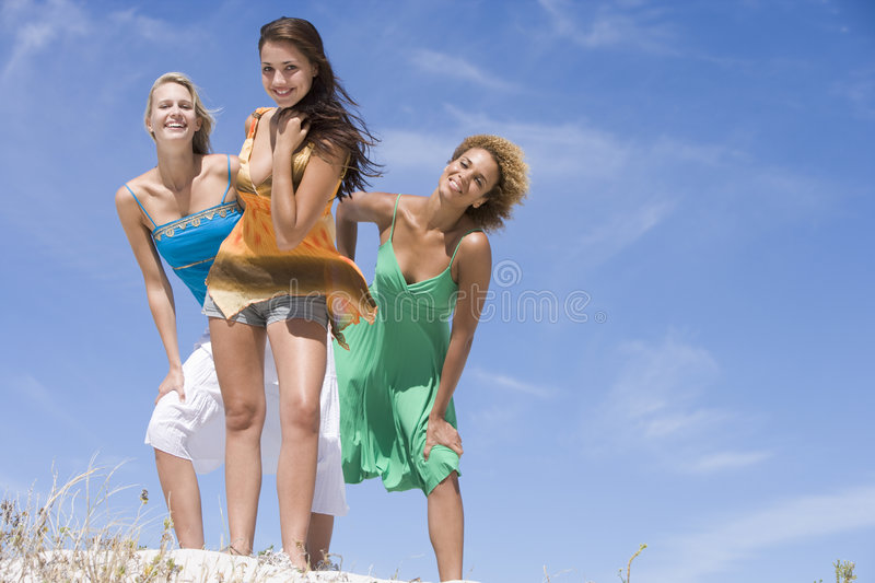 Three female friends relaxing at beach stock photography