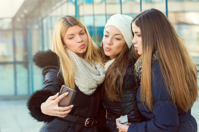 Three female friends taking selfie. Outdoors. Winter time shopping girls stock photography