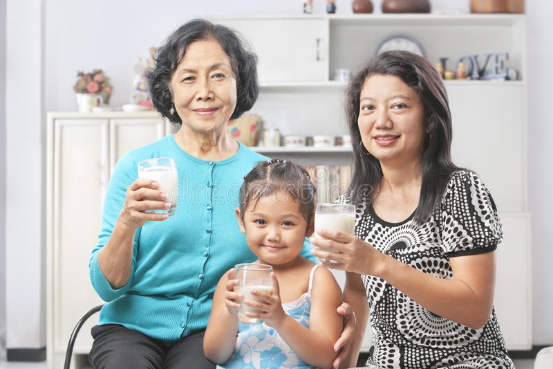 Three female generation holding glass of milk stock photo