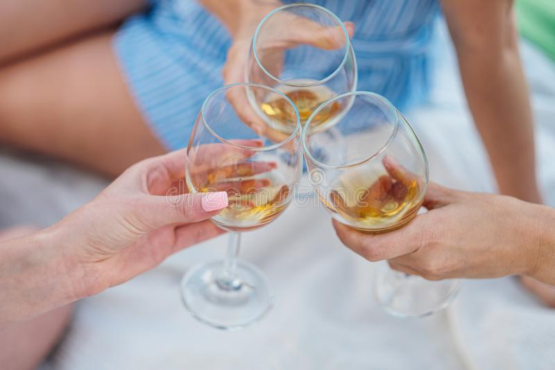 Three female hands with glasses of white wine. Toast, congratulations on an outdoor picnic. The concept of relaxation stock photo