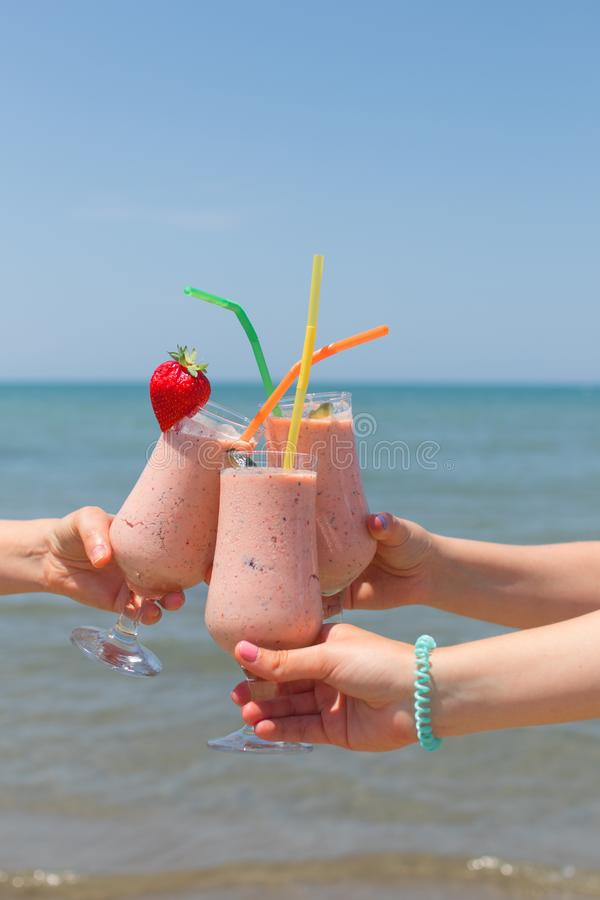Three female hands are holding strawberry milkshakes on the background of the sea stock photos