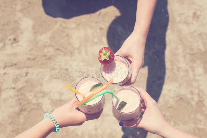 Three female hands are holding strawberry milkshakes on the background of the sea stock photo
