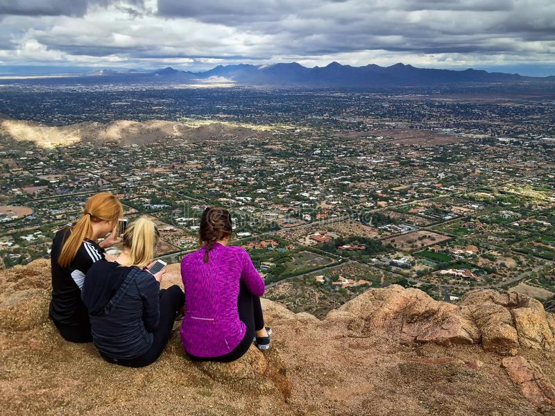 Three female hikers on mountain summit with city view, Camelback Mountain, Phoenix, Arizona, USA stock image