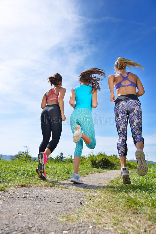 Three Female Joggers running together outdoors. Three Female Joggers running together on trail outdoors royalty free stock image
