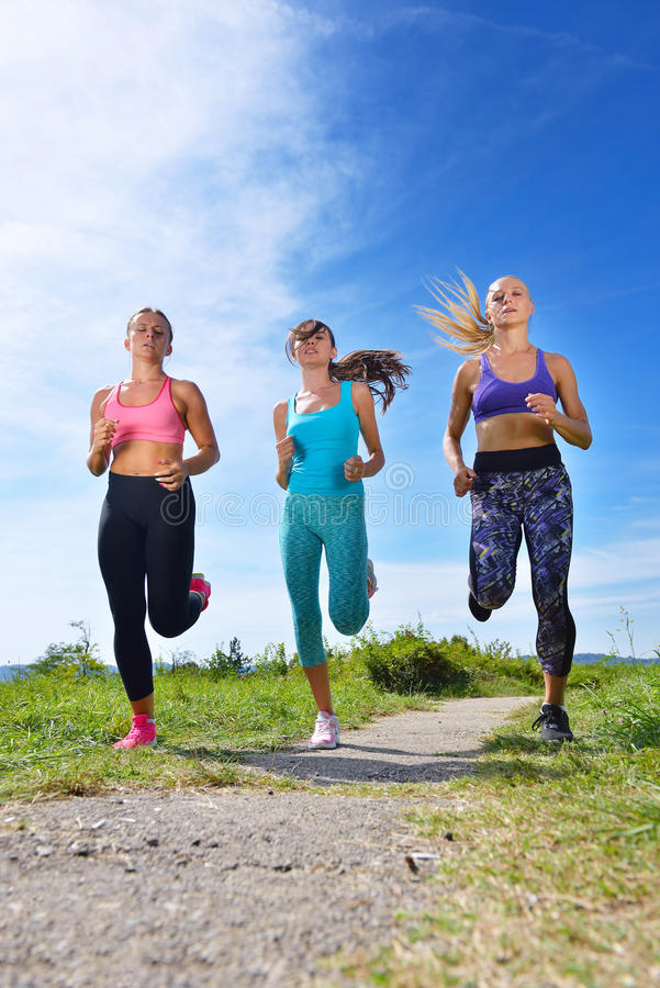 Three Female Joggers running together outdoors. Three Female Joggers running together on trail outdoors royalty free stock images
