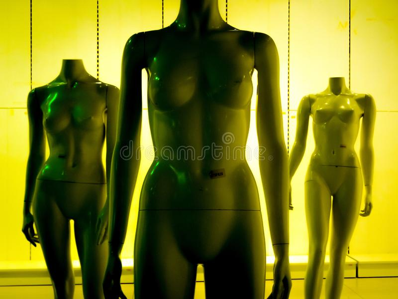 Three female mannequins in yellow-green tint stock photos