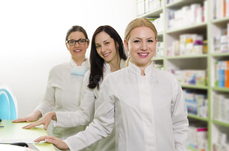 Three female pharmacists on work. Three female pharmacists standing in row and smiling, medicine shelves in background stock images