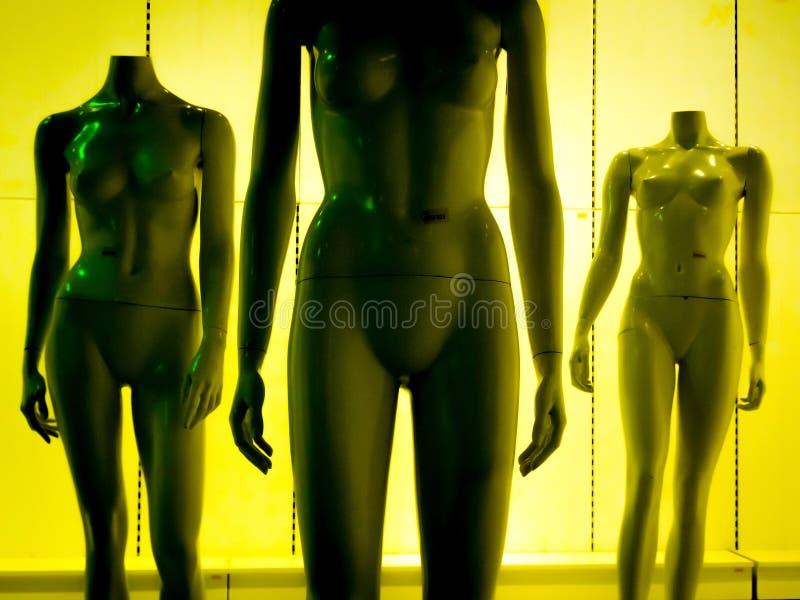 Three female plastic fiber mannequinsin yellow-green tint 2 stock images