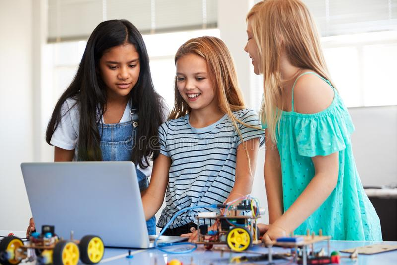 Three Female Students Building And Programing Robot Vehicle In After School Computer Coding Class royalty free stock photos