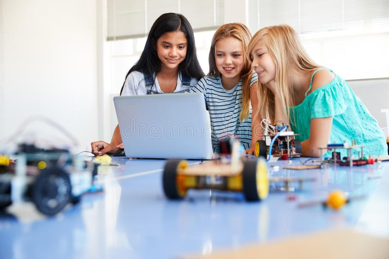 Three Female Students Building And Programing Robot Vehicle In After School Computer Coding Class royalty free stock images