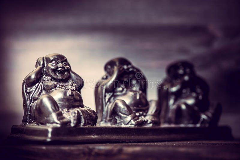 Three figures of Buddah philosophy. Three figures of Buddha philosophy on wooden background stock image