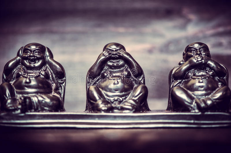 Three figures of Buddah philosophy. Three figures of Buddha philosophy on wooden background stock images