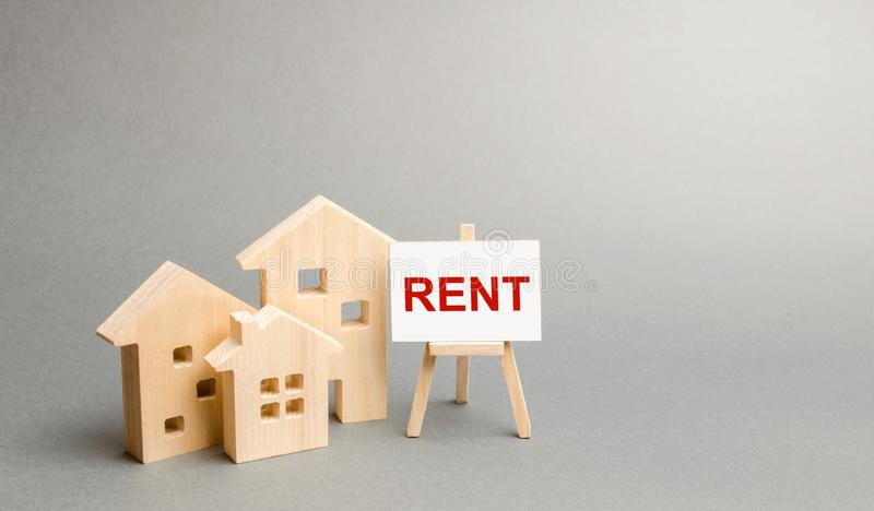 Three figures of houses and an easel with the word rent. The concept of temporary rental housing and real estate. Realtor services. Search for optimal options stock photo