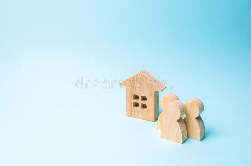 three figures of people and a wooden house on a blue background. The concept of affordable housing and mortgages for buying a home stock photos