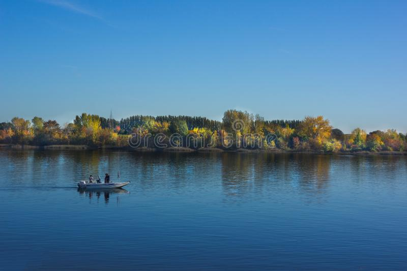 Fishermen on Yakima River Washington. Three fishermen take to the river in the early morning in search of fish in the Yakima River. Bright fall colors line the royalty free stock photo