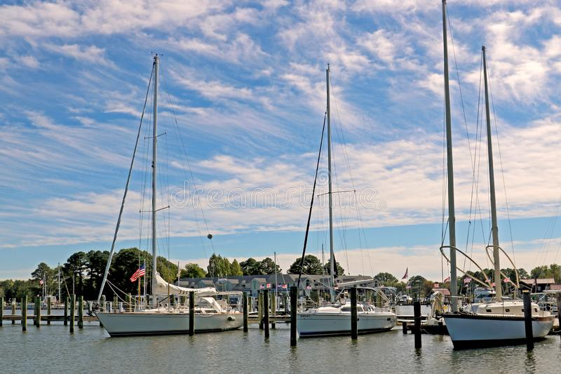 Three fishing boats docked in a harbor under a cloudy blue sky royalty free stock photo