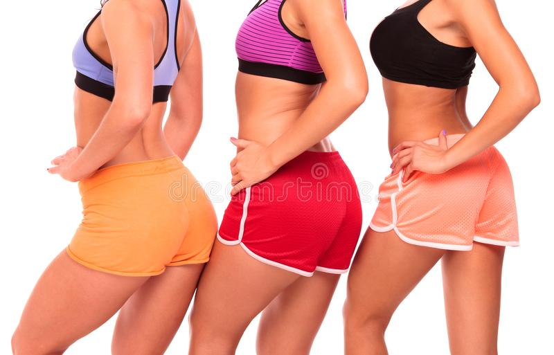 Three fit girls posing against white background royalty free stock photos
