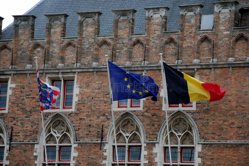 Three flags. Flags of Belgium, the European Union and the city of Bruges on a background of an old building stock image