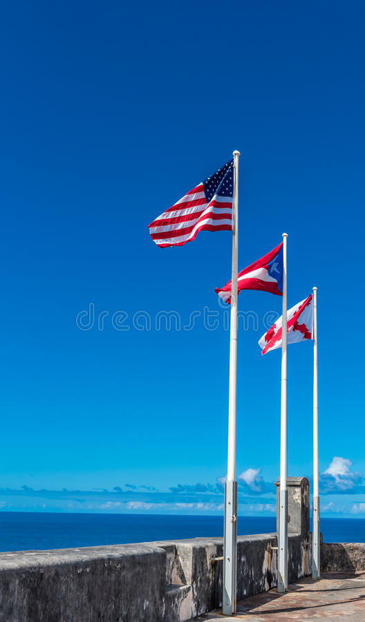 Three flags flying from Castillo de San Cristobal. The US flag, PR flag and the flag of the castle royalty free stock photos