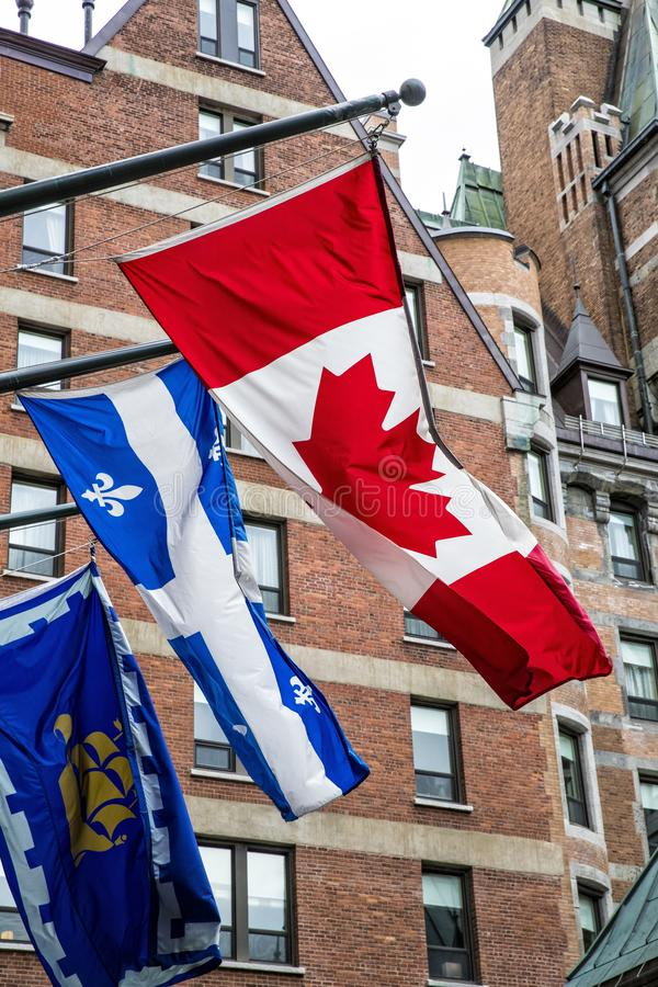 Three flags outside of entrance into Fairmont Hotel in Quebec City stock images
