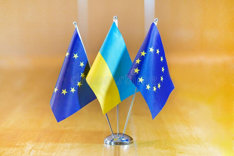 Flags of European Union and Ukraine. Three flags on the table. Flags of Ukraine, European Union. Flags of European Union and Ukraine on the table during a stock image